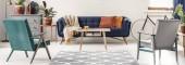 Fotografie Echtes Foto von Grün und grau Sessel stehen neben einem gemusterten Teppich, mit Blick auf blauem Sofa mit orange Kissen und ein Holztisch in bunte Wohnzimmer Interieur