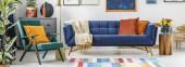 Fotografie echtes Foto eines kristallgrünen Sessels neben einer blauen Couch im Wohnzimmer mit Blumen auf einem Holzhocker und Malerei an der Wand
