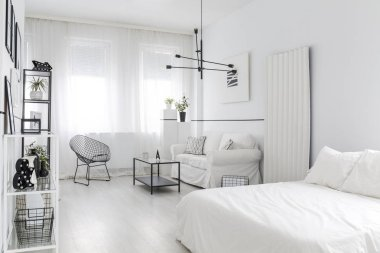 Black armchair next to a table and sofa in white, bright flat interior with bed and poster on the wall