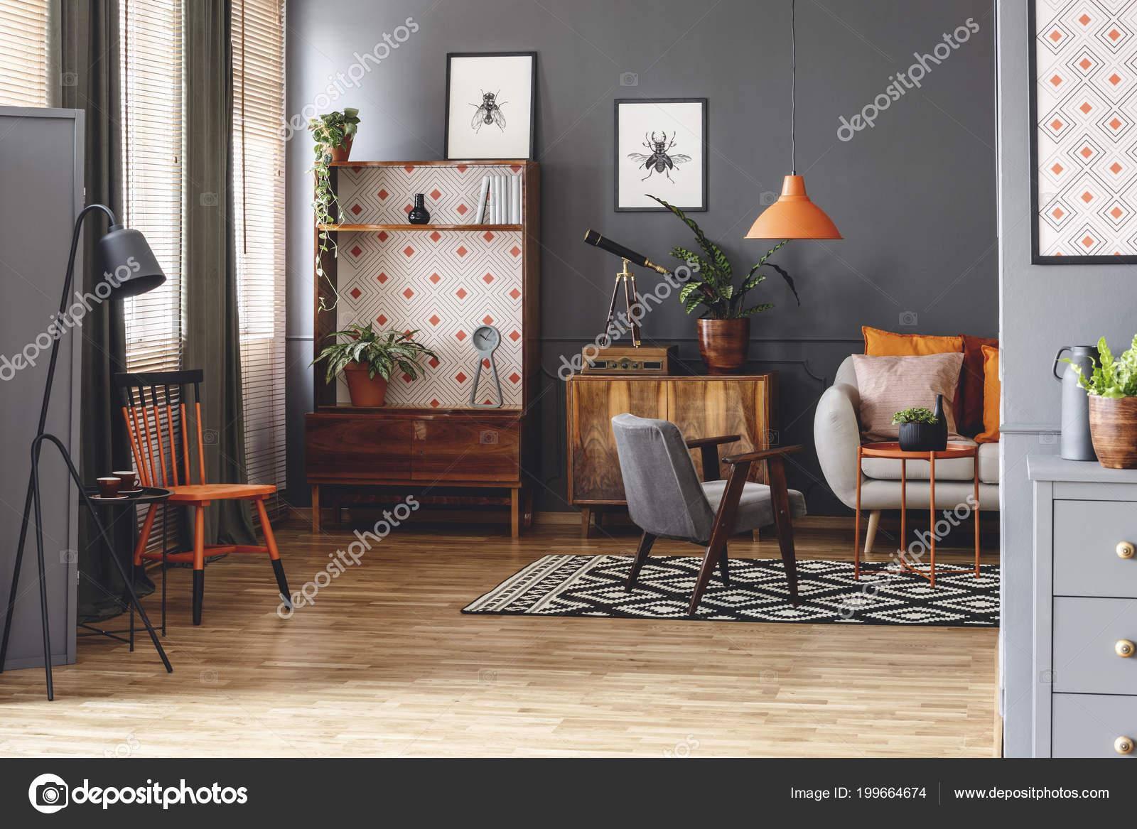 Zwarte lamp naast oranje stoel grijs woonkamer interieur met