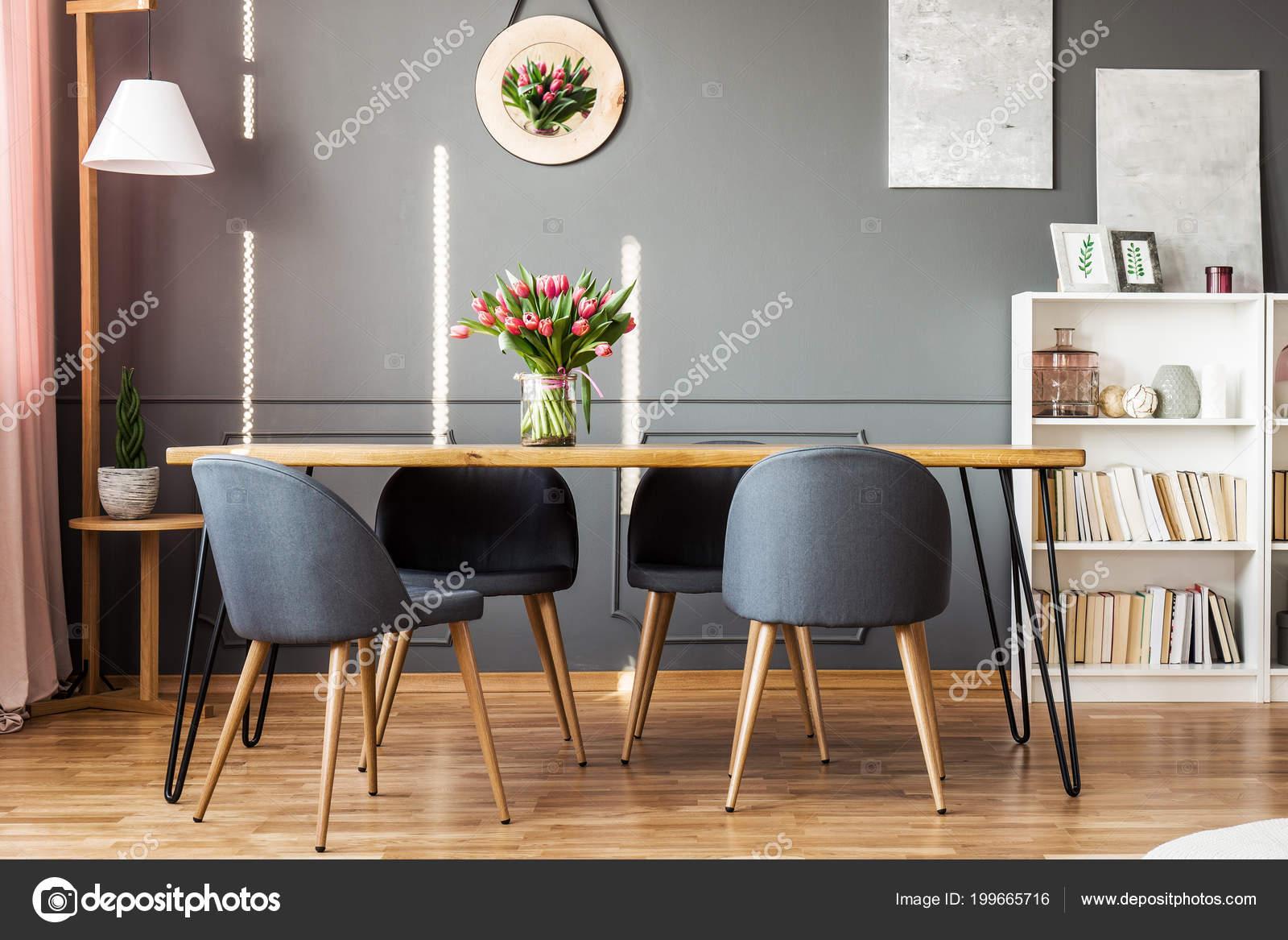 Houten eettafel grijze stoelen boekenplank roze tulpen het interieur