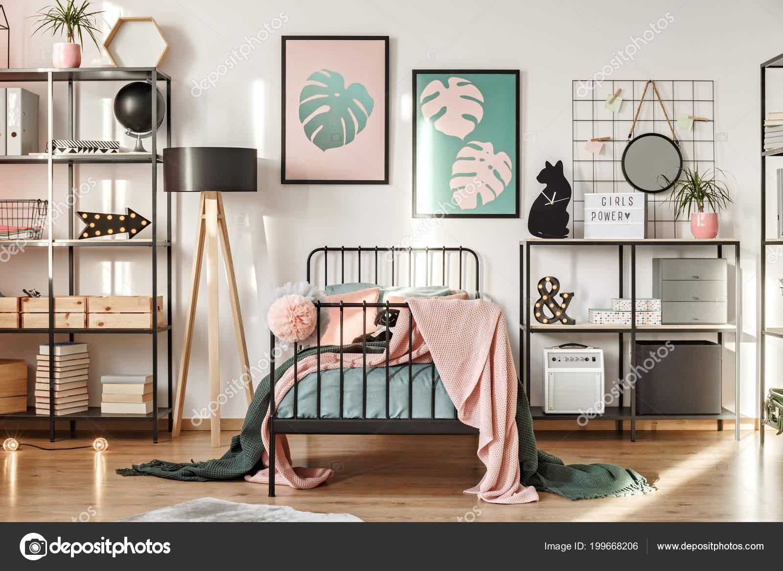 Metalen rekken met decoraties botanische posters comfortabele bed
