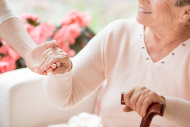Close-up of caregiver supporting smiling senior woman with walking stick