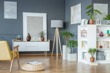 Wooden lamp placed in the corner of living room interior with fresh potted plants, gallery and books