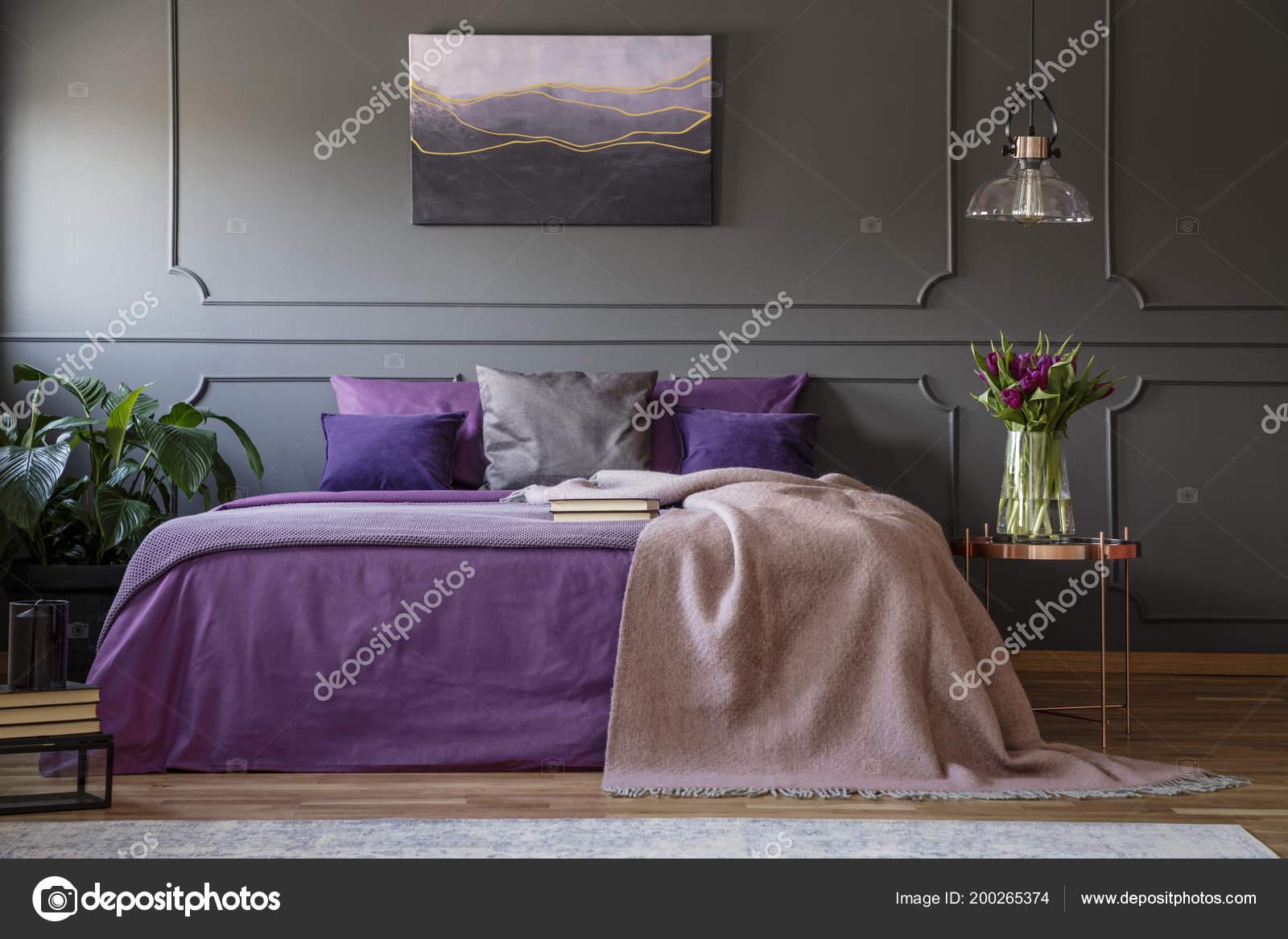 Paarse Slaapkamer Lamp : Lamp boven tafel van koper met bloemen naast bed met u stockfoto