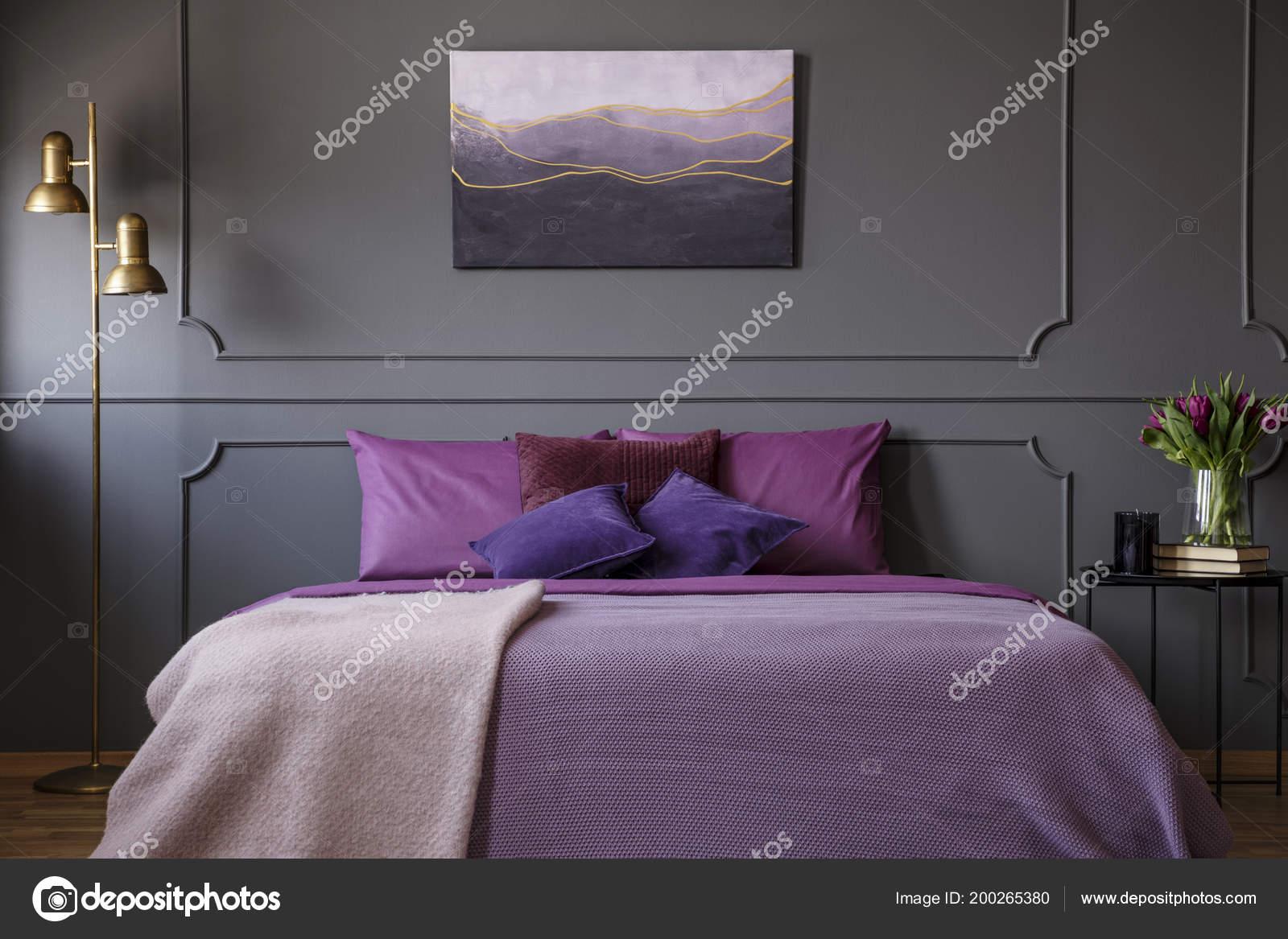 Paarse Slaapkamer Lamp : Gouden lamp naast paarse bed tegen grijs muur met molding