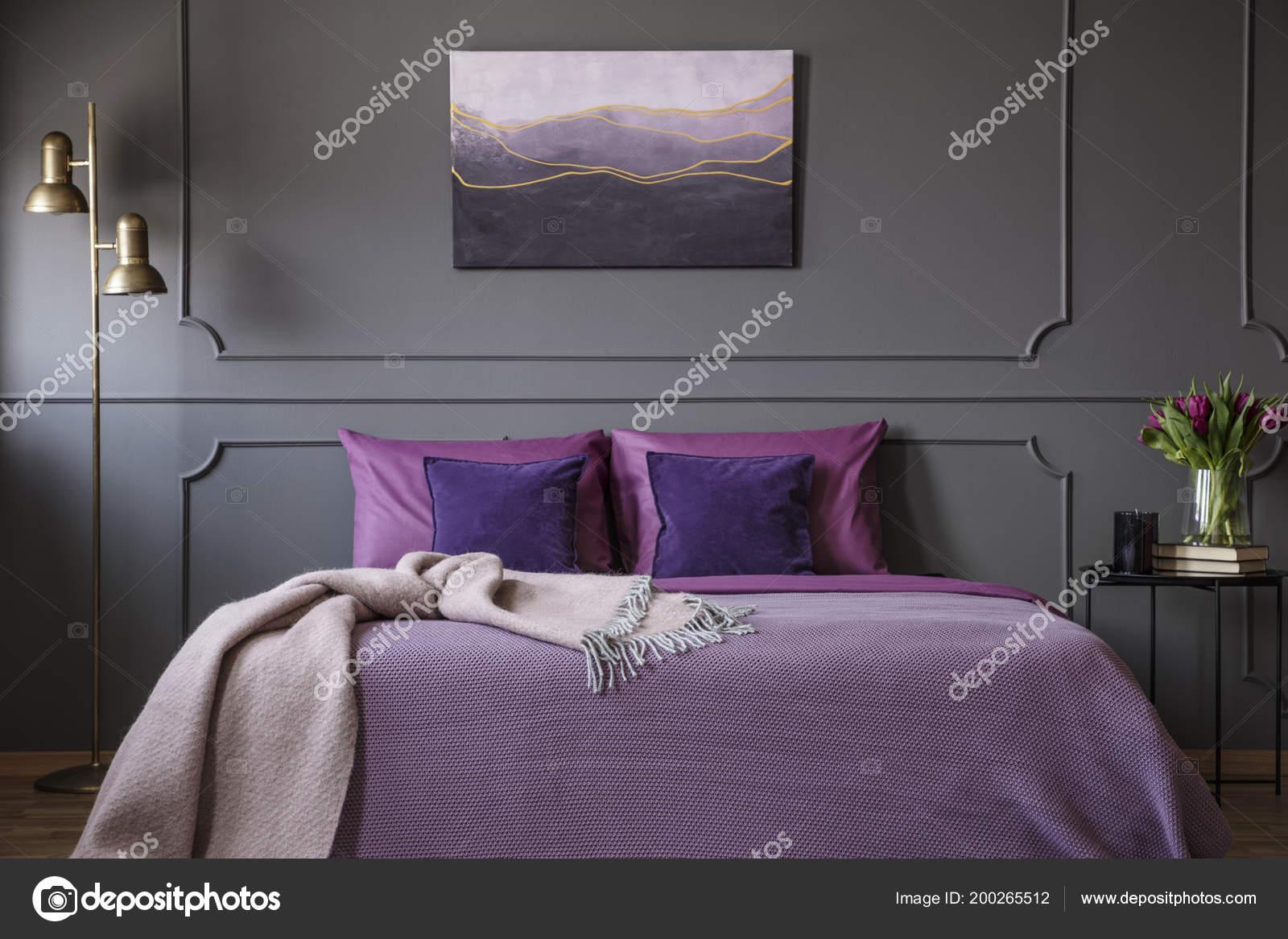 roze deken op violet bed in elegante slaapkamer interieur met schilderen op grijs muur met molding foto van photographeeeu