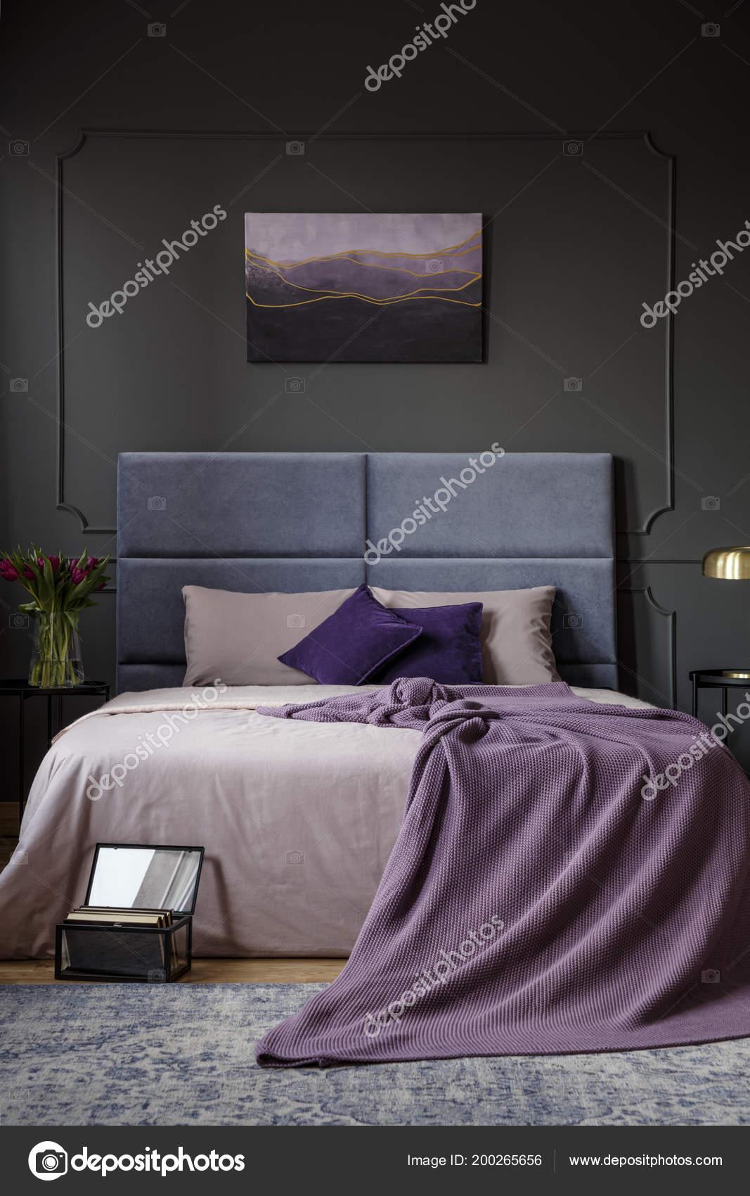 paarse deken het bed donkere slaapkamer interieur met een schilderij stockfoto