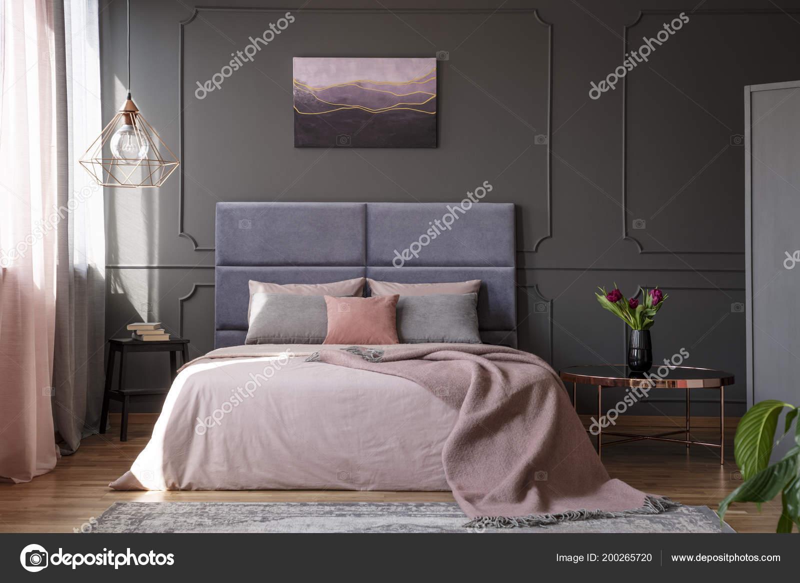 Roze Grijze Slaapkamer : Tulpen koperen tafel naast roze bed tegen grijs muur met