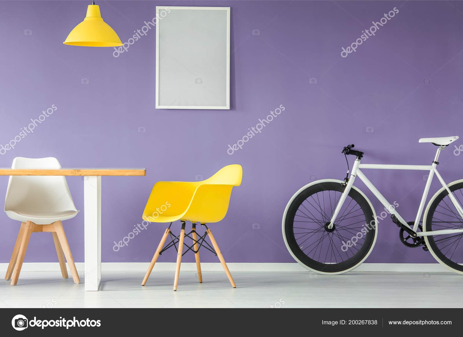 Minimale modern interieur met een witte gele stoel een fiets