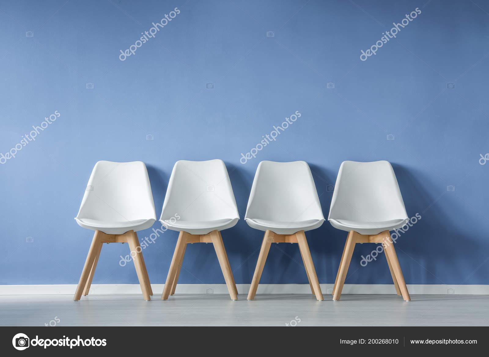 Vista frontale una fila sedie bianche moderne semplici contro
