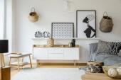 Fotografie Poster und Teller über dem Holzschrank im Boho-Wohnzimmer mit grauem Sofa. echtes Foto