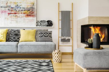 Pillows on grey settee in warm living room interior with painting and fireplace. Real photo
