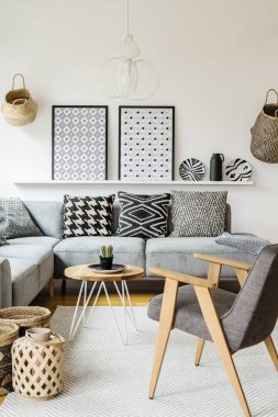Grey wooden armchair in modern living room interior with posters above grey sofa. Real photo