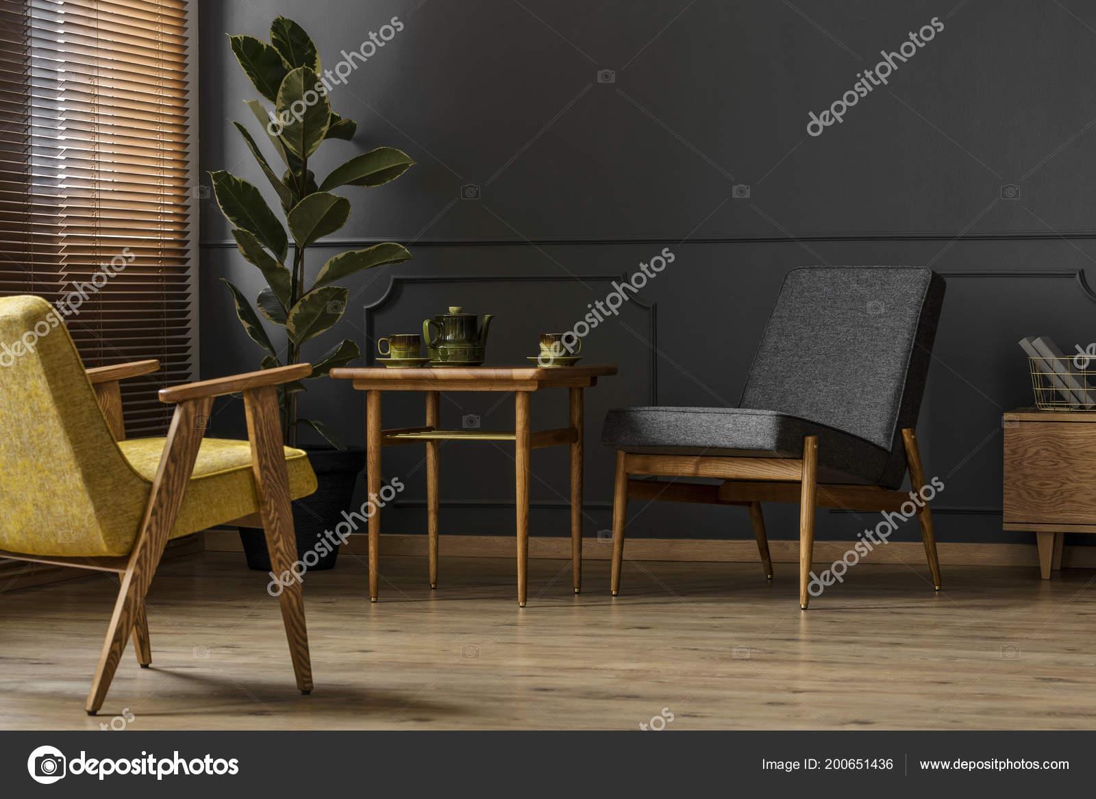 eenvoudige donkere woonkamer retro interieur concept met twee stoelen kruk stockfoto