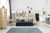 Photo Green folded mattress and cushions with pattern placed in Scandinavian living room interior with wooden furniture and simple gallery