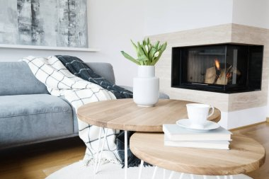 Patterned blanket on grey sofa and flowers on a table in warm living room interior with fireplace