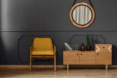 """Картина, постер, плакат, фотообои """"простой интерьер черной комнаты с деревянным полом, желтым стулом, зеркалом и шкафом зеркало раме зеркала настенное круглые большие"""", артикул 200651506"""