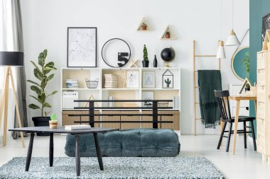 Black table on carpet near green futon in scandi living room interior with poster and ficus