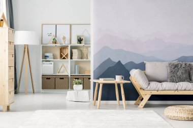 Open space living room interior with mountain wallpaper, light grey sofa and white rack with decor