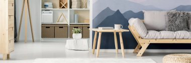 Panorama of a wooden frame sofa and a side table by a mountains wallpaper in a scandinavian style, white living room interior