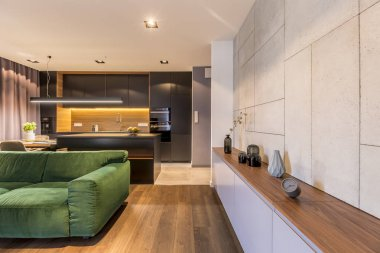 Wooden cupboard with vases and clock in modern elegant living room interior with green velvet sofa and dark kitchen corner