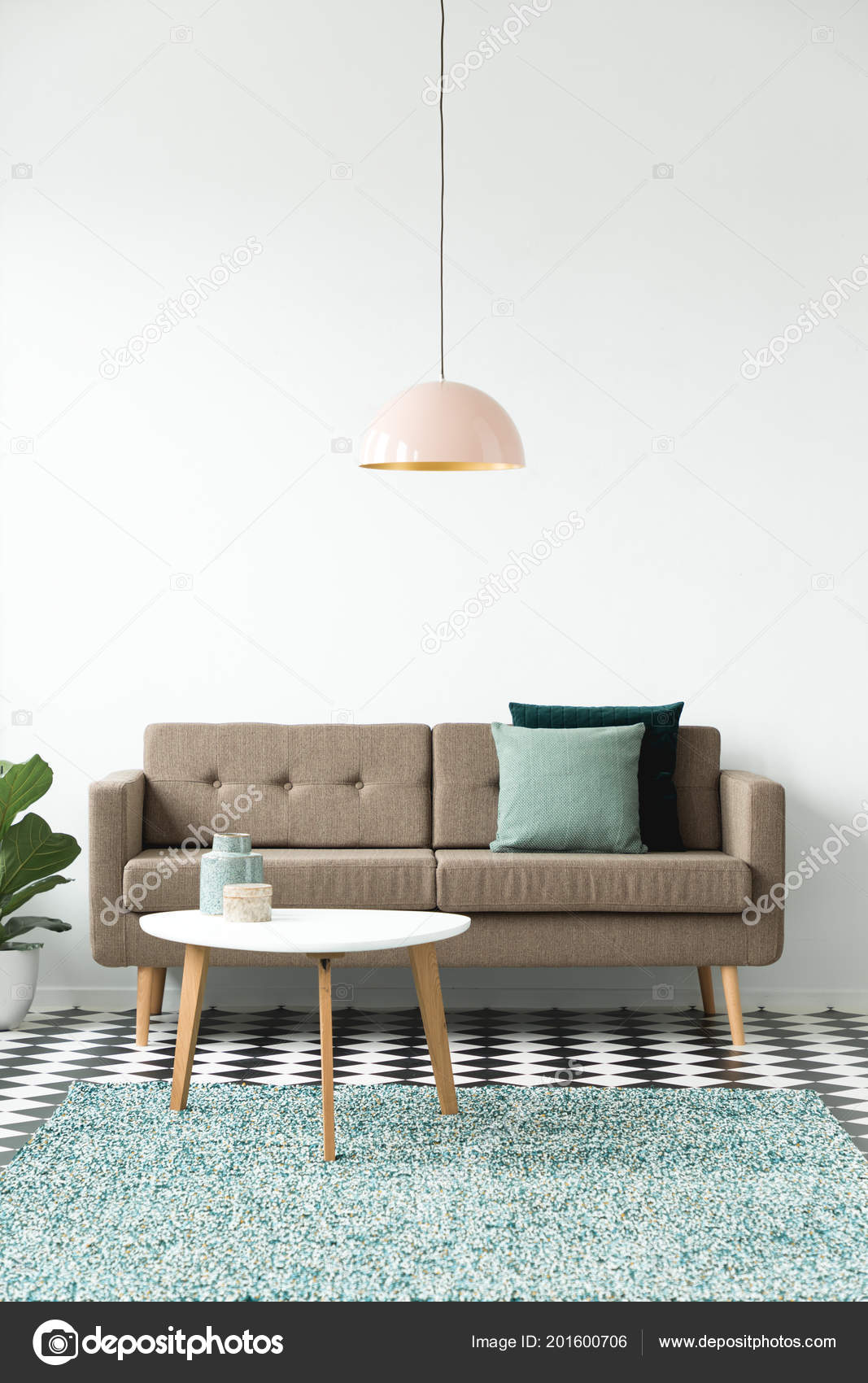 Front view of a sofa with pillows coffee table chandelier and green carpet set on a white wall in living room interior photo by
