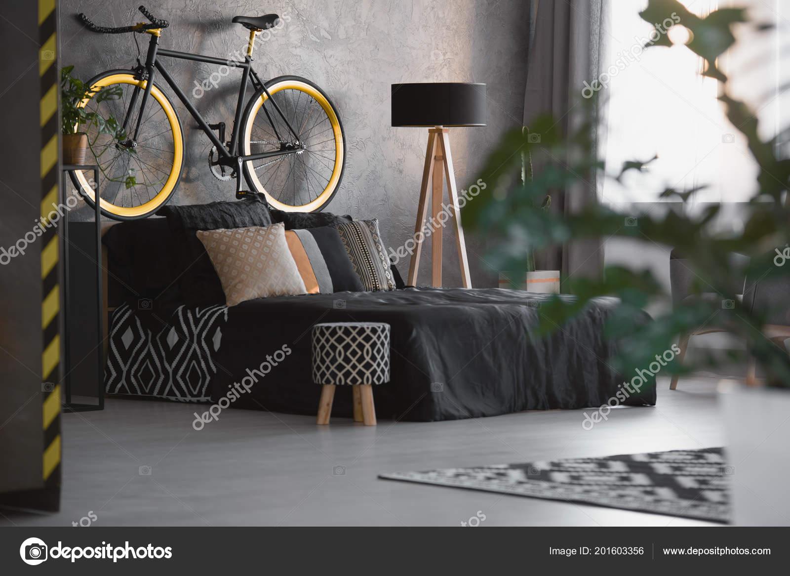 Piccolo sgabello con piedi modello bianco nero accanto letto all