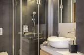 Koupelny interiér s bílým, Keramické umyvadlo a sprcha kabina se skleněnými dvířky. Reálné Foto