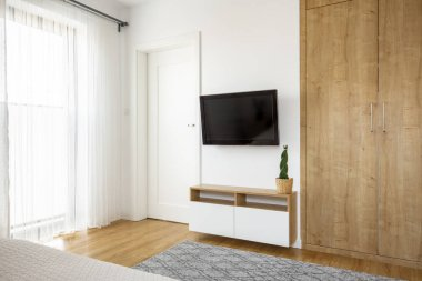 Wooden wardrobe next to television on white wall in hotel bedroom interior with door. Real photo