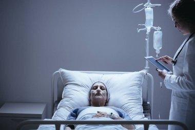 Doctor with tablet next to bed with dying elderly woman with cancer in the clinic