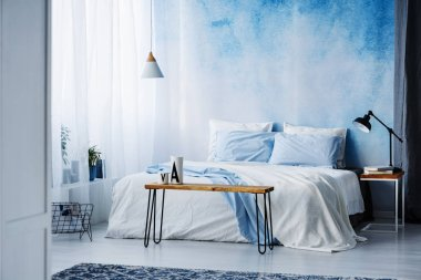 Lamp on wooden table next to a blue and white bed in bedroom interior with ombre wall