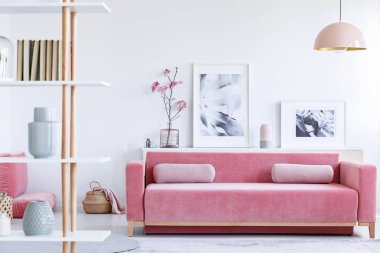 Real photo of a pink couch with pillows in front of a shelf with posters and flowers in bright living room interior with a hanging lamp and shelf with books in the front