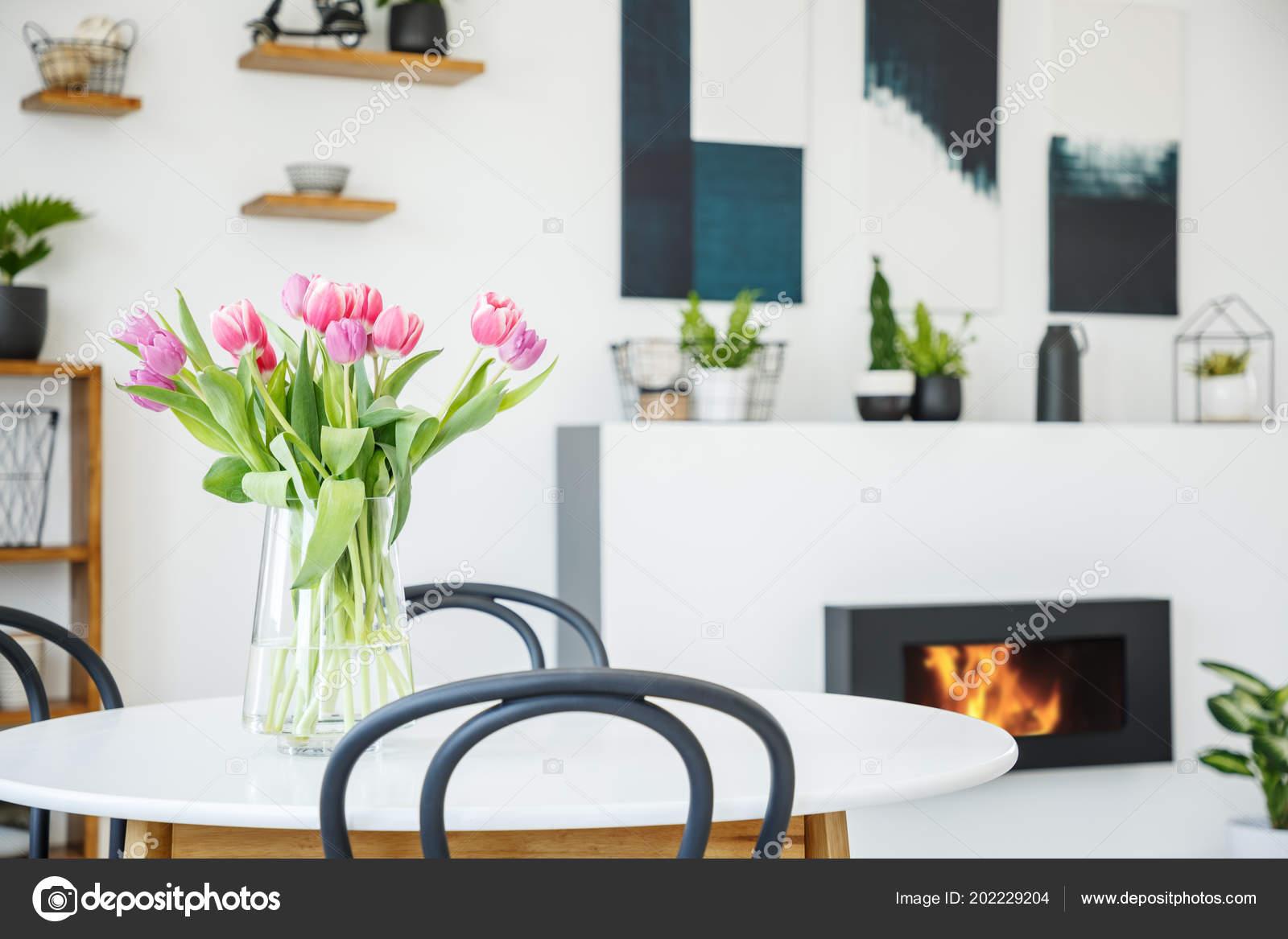 Roze tulpen eettafel witte kamer interieur met planten posters