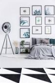 Fényképek Valódi kép egy ágyban mellette egy polc a növények és a fekete lámpa egy hálószoba belső fal tele a plakátok és fekete-fehér szőnyeg