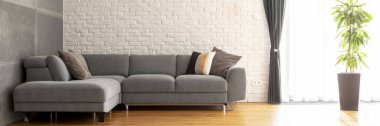 Grey corner sofa with decorative cushions in the real photo of bright living room interior with brick wall, fresh green plant and window with drapes