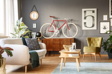 Real photo of a cozy sitting room interior with comfortable white sofa with blanket and pillows, green armchair, small table, red bike, rug on wooden floor and sketches on dark gray wall