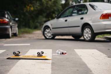 Skateboard and child's shoe on a pedestrian crossing after dangerous traffic incident