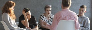 Difficult teenagers listening to psychotherapist during meeting of support group