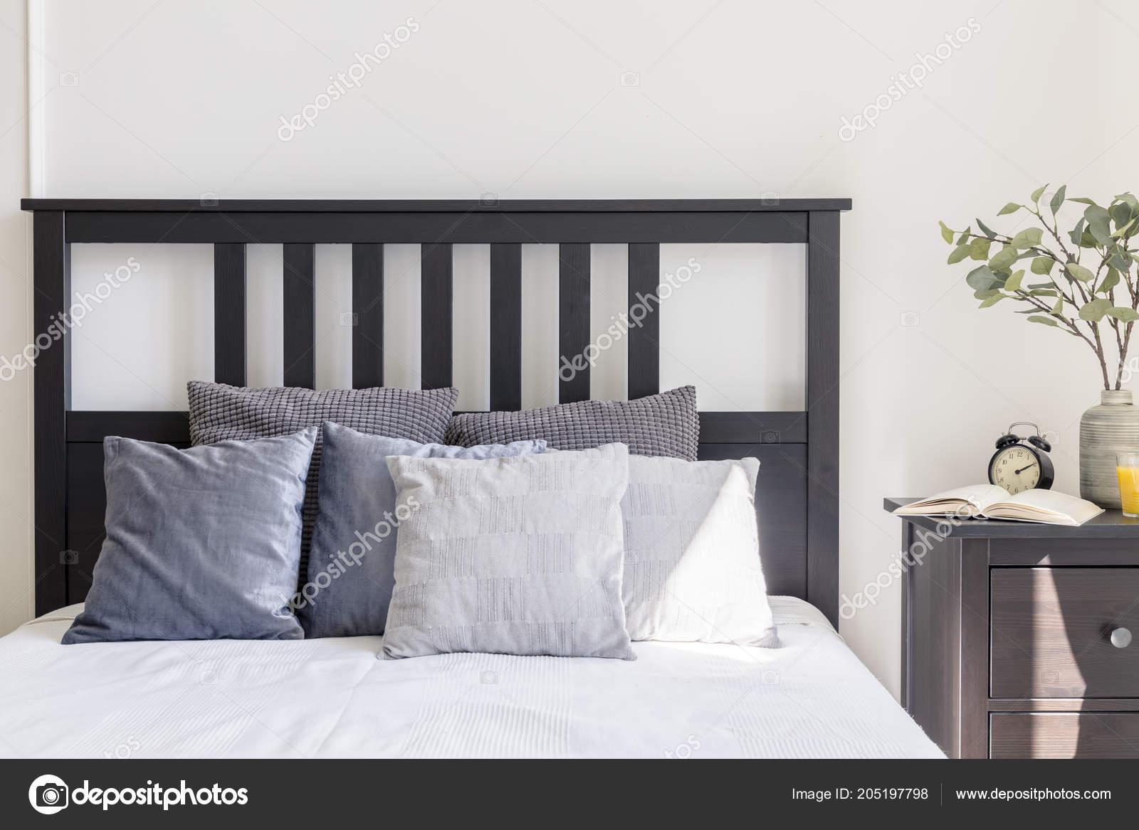 Grijze witte kussens bed met zwarte hoofdeinde eenvoudige slaapkamer