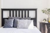 Fotografie Šedé a bílé polštáře na postel s černým čelem v interiéru jednoduché ložnice. Reálné Foto