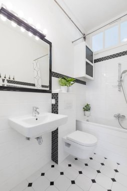Mirror above washbasin in black and white bathroom interior with toilet and bathtub. Real photo