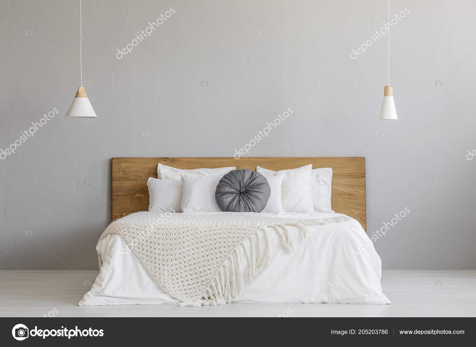 brei de deken op houten bed tegen grijs muur in minimale slaapkamer interieur met lampen echte foto met een plek voor uw nachtkastje foto van