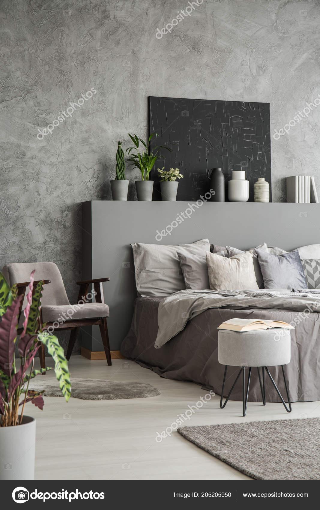 intérieur chambre coucher couleurs terre avec grand lit fauteuil