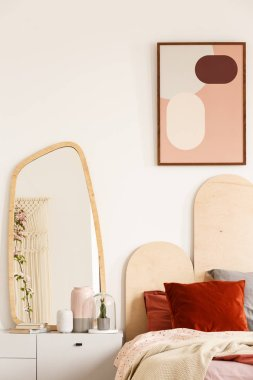 Mirror on white cabinet next to bed with red cushions under poster in pastel bedroom interior. Real photo