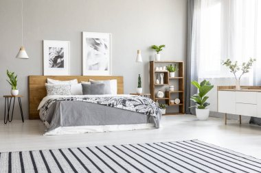 Striped carpet in spacious bright bedroom interior with posters above wooden bed. Real photo