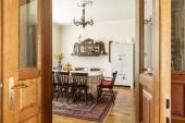Reálné fotografie interiéru starožitný jídelní velký stůl, židle, skříňky na stěnu a koberec. Zobrazit přes dveře