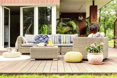 Garden table with fruits and fresh orange juice standing on wooden terrace with plants, armchair and sofa with pillows