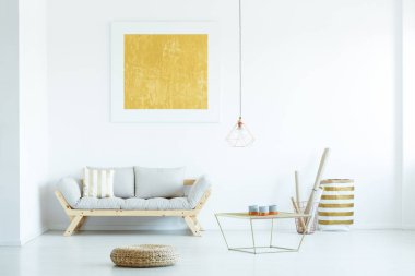 Real photo of a couch with a stripped cushion standing next to a table and baskets in white living room interior with a painting on a wall