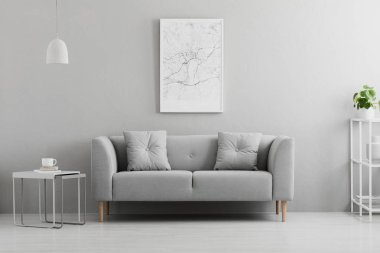 Poster above grey couch in minimal living room interior with lamp above table. Real photo stock vector